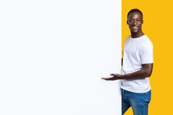 Handsome black man showing blank advertisement board, standing on yellow studio background. Smiling african american guy posing next to big white placard for text or advertising, panorama