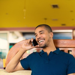 Handsome black man talking on smart phone, looking aside and smiling. He is at cafe bar.