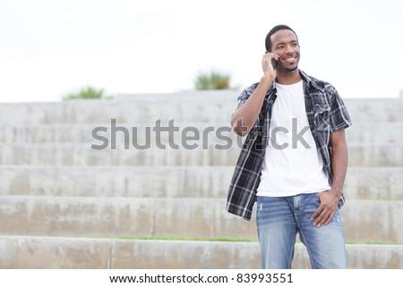 Handsome black man walking on a mobile phone