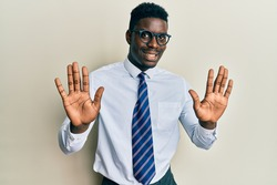 Handsome black man wearing glasses business shirt and tie showing and pointing up with fingers number ten while smiling confident and happy.