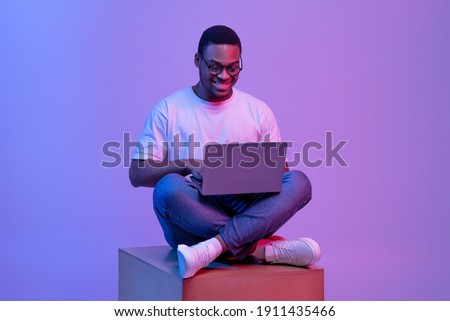 Handsome Black Programmer Guy Using Laptop Computer, Sitting On Big Cube In Neon Lighting, Cheerful African American Man In Glasses Working Or Study Online Over Purple Studio Background, Copy Space