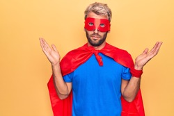 Handsome blond man wearing super hero costume with mask and cape over yellow background clueless and confused with open arms, no idea and doubtful face.