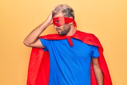 Handsome blond man wearing super hero costume with mask and cape over yellow background surprised with hand on head for mistake, remember error. Forgot, bad memory concept.