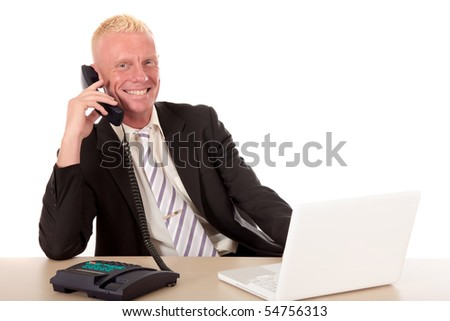 Handsome blond smiling mid forties businessman at desk with laptop making phone call.  Studio white background