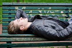 Handsome blond young man lying down on green, wooden park bench, looking up