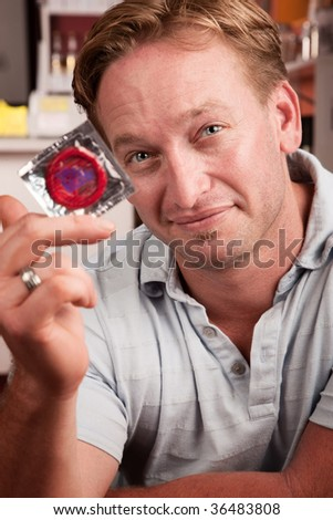 Handsome blonde man holding a wrapped condom