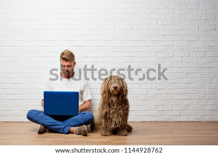 handsome blonde man with a dog and a portable computer