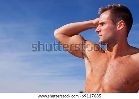 Handsome body builder on blue sky