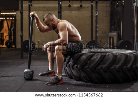 handsome bodybuilder with closed eyes is resting after doing sledgehammer exercises at the gym. full length side view photo