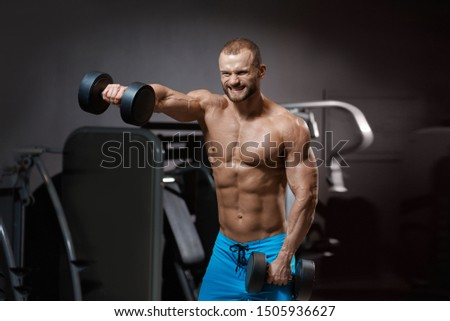 Handsome bodybuilders grimace of effort posing with dumbbells in modern gym