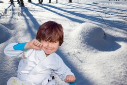 Handsome boy in judo uniform. Deep snow covered the ground. Judo is a humane modern martial art. New Years is soon. Frosty snowy sunny day in the winter forest.