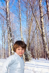Handsome boy in judo uniform. Deep snow covered the ground. New Years is soon. Frosty snowy sunny day in the winter forest. Judo is a humane modern martial art