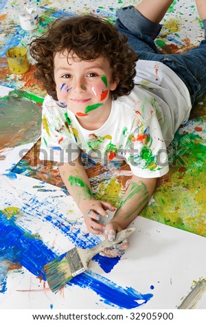 Handsome boy playing with painting with the background painted