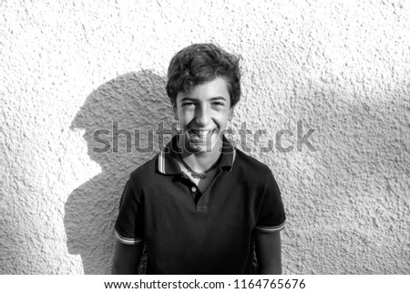 Handsome boy poses together white wall of house #1164765676
