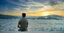 Handsome boy sitting on the beach at sunset, young man sit on the beach copy space, Lonely boy sits alone on the rocky coast and enjoying sunset view