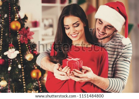 Handsome Boyfriend Give Present. Xmas Tree on Background. Christmas Celebration. Woman in Hugs. Male and Female Celebrating. Christmas at Home. Family Concept. Male Dressed in Santa Claus Hat.