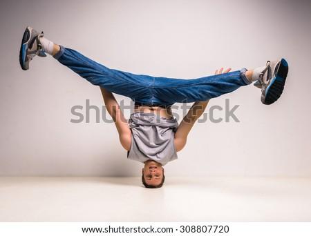 Handsome break dancer standing on his head at studio over white background.
