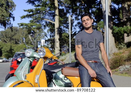 Handsome brunet young man in casual clothing stand near yellow scooter