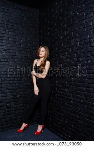Handsome brunette girl wear on black and red high heels, posing at studio against dark brick wall. Studio model portrait. #1073193050