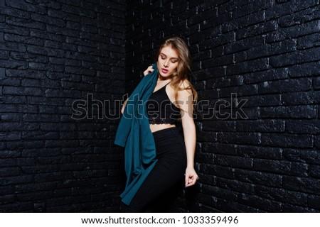 Handsome brunette girl wear on black, posing at studio against dark brick wall. Studio model portrait. #1033359496