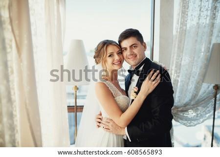 Handsome brunette groom and dark blonde bride hug before bright window #608565893