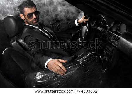 Handsome brutal man in the car. Luxury. Night life.