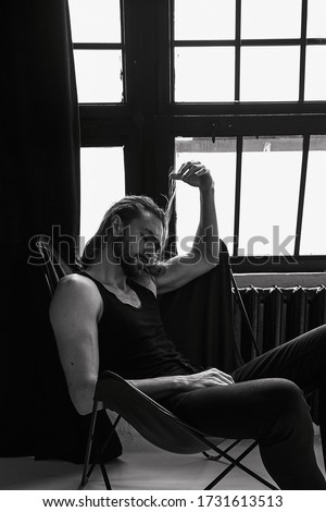 Handsome brutal man wiht beard cool long hair style.Sexy Businessman. Confident, attractive, stylish. Fashion shooting. Actor. Black and white.