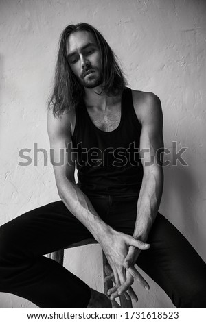 Handsome brutal man with beard and cool long hair.Sexy  athletic body. Confident, attractive, stylish. Fashion shooting. Actor. Black and white