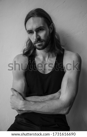 Handsome brutal man with beard and cool long hair.Sexy Businessman. Confident, attractive, stylish. Fashion shooting. Actor. Black and white