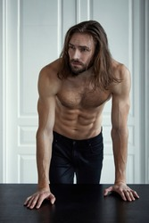 Handsome brutal man with beard and cool long hair.Sexy topless athletic body . Confident, attractive, stylish. Fashion shooting. Actor.
