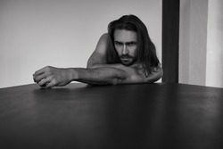 Handsome brutal man with beard and cool long hair.Sexy topless athletic body. Confident, attractive, stylish. Fashion shooting. Actor. Black and white
