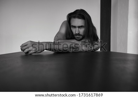 Handsome brutal man with beard and cool long hair.Sexy topless athletic body. Confident, attractive, stylish. Fashion shooting. Actor. Black and white Stock photo ©