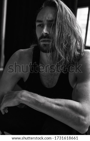 Handsome brutal man with beard cool long hair style.Sexy Businessman. Confident, attractive, stylish. Fashion shooting. Actor. Black and white