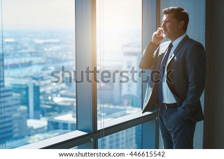 Handsome business CEO with designer stubble, talking confidently on his mobile phone while looking out of large windows in a top floor office at the city below