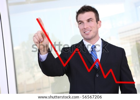 Handsome  business man drawing a graph on a glass window at office - focus is on man