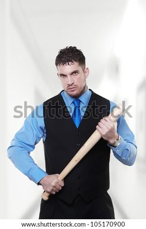 Handsome business man holding a baseball bat looking at camera