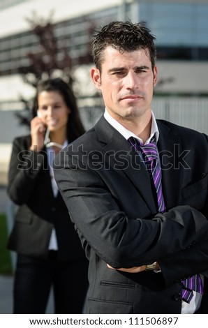 Handsome business man idly and looking at camera while bussineswoman is talking by phone on background