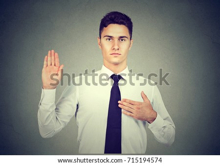 Handsome business man making an oath promise on gray background