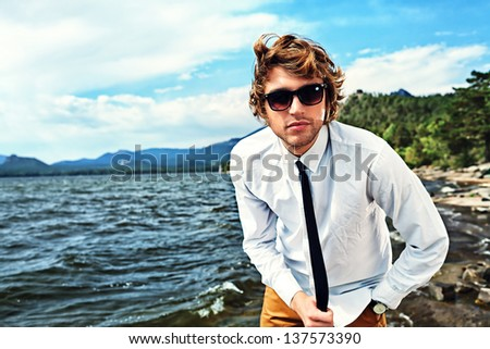 Handsome business man standing on a seaside and looking to the camera.