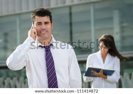 Handsome business man talking by cellphone while his secretary is taking notes - stock photo