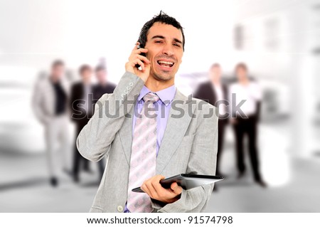 Handsome business man using a tablet and talking on the phone