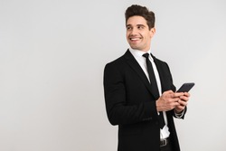 Handsome business man wearing suit standing isolated over gray background, using mobile phone
