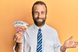 Handsome business man with beard and long hair holding bunch of 10 euro banknotes celebrating achievement with happy smile and winner expression with raised hand