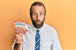 Handsome business man with beard and long hair holding bunch of 10 euro banknotes scared and amazed with open mouth for surprise, disbelief face