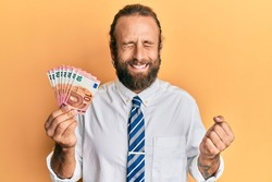 Handsome business man with beard and long hair holding bunch of 10 euro banknotes screaming proud, celebrating victory and success very excited with raised arm