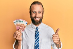 Handsome business man with beard and long hair holding bunch of 10 euro banknotes smiling happy and positive, thumb up doing excellent and approval sign