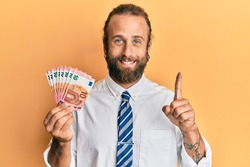 Handsome business man with beard and long hair holding bunch of 10 euro banknotes smiling with an idea or question pointing finger with happy face, number one