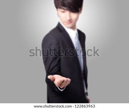 handsome Business man with empty hand on gray background, great for you design, asian model - stock photo