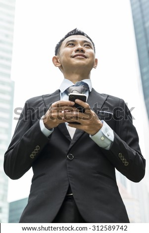 handsome business man writing email or message on phone, model is a asian male