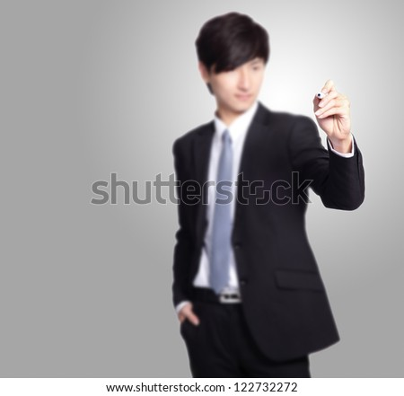 handsome Business man writing with marker pen in the air isolated on gray background, great for you add any text or graph